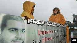 Supporters stand in the rain with a sign outside of US District Court in Boston, October 27, 2011, during the first day in the trial of Tarek Mehanna, 29, of Sudbury, Massachusetts, who is charged with providing support to a terrorist group.