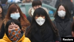 FILE - Commuters wearing masks make their way amid thick haze in the morning in Beijing February 26, 2014.
