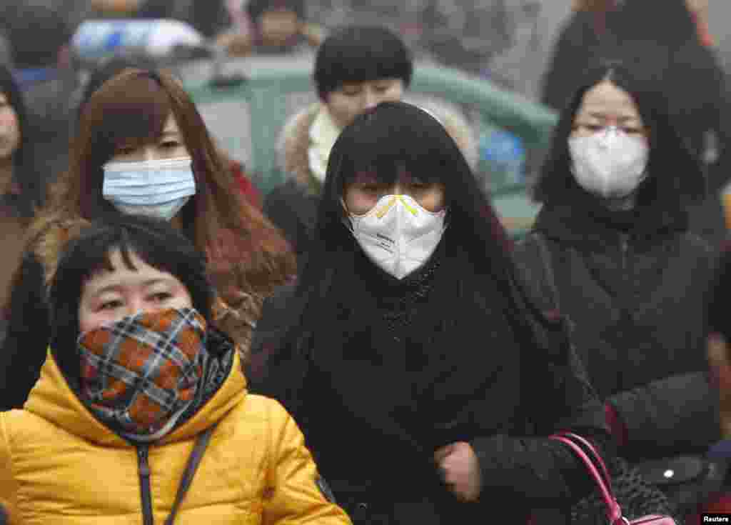 Commuters wearing masks make their way amid thick haze in the morning in Beijing, Feb. 26, 2014.