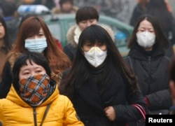 FILE - Commuters wearing masks make their way amid thick haze in the morning in Beijing, Feb. 26, 2014.