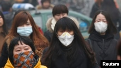 FILE - Commuters wearing masks make their way amid a thick morning haze in Beijing.