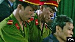 Pastor Thadeus Nguyen Van Ly (kanan) dikawal oleh polisi dalam persidangan di pengadilan Vietnam (foto: dok.).