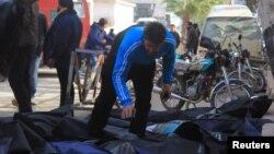 Một người đàn ông cố gắng xác định các thi thể sau những gì các nhà hoạt động cho biết là cuộc không kích được thực hiện bởi các lực lượng không quân Nga tại thành phố Idlib, Syria, ngày 20/12/2015.