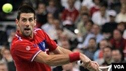 Novak Djokovic mengembalikan bola lawannya, petenis Perancis Gilles Simon, dalam Piala Davis yang saat ini imbang 1-1.