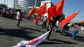 A Chinese woman drags a Japanese flag on the ground during a protest march in Beijing last September. The media plays a large role in stoking anti-Japanese sentiment.