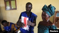 FILE - An election official shows to a woman how to cast her ballot during Liberia's presidential election in Monrovia, Liberia, October 10, 2017.