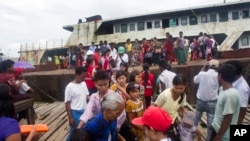 FILE - Fleeing Buddhist Rakhine residents arrive by ship from the unrest in Maungdaw region at the jetty, Aug. 29, 2017, in Sittwe, Rakhine State, western Myanmar.