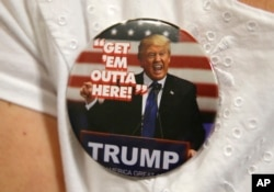 FILE - A supporter of Republican presidential candidate Donald Trump wears a campaign button before the start of a rally in Spokane, Wash.