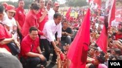 Calon Presiden dari PDI Perjuangan Jokowi bersalaman dengan para ribuan simpatisan dan kader PDI Perjuangan yang menghadiri kampanye terbuka Minggu 16 Maret 2014 di Gelanggang Olah Raga Cendrawasih Cengkareng Jakarta. (VOA/Andylala Waluyo)