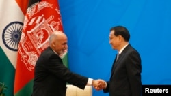 Chinese Premier Li Keqiang (R) shakes hands with Afghan President Ashraf Ghani at the opening ceremony of the 4th Ministerial Conference of Istanbul Process of Afghanistan at the Diaoyutai Guesthouse in Beijing, October 31, 2014.