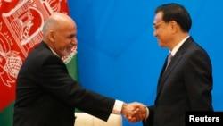افغان صدر اور چین کے وزیراعظم مصافحہ کر رہے ہیں