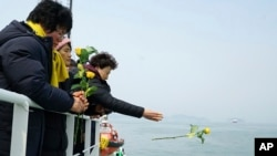 In this photo provided by South Korean Ministry of Oceans and Fisheries, a relative of missing passengers of the sunken Sewol ferry hurls a flower during religious services in waters off Jindo, South Korea, March 28, 2017.