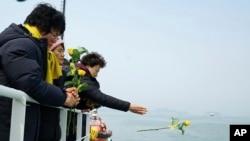 Seorang yang anggota keluarganya termasuk dalam korban yang hilang saat tenggelamnya kapal feri Sewol, melemparkan bunga mawar ke laut Jindo saat diadakan doa bersama untuk mengenang para korban, 28 Maret 2017. (Foto: dok).
