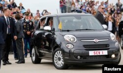 Pope Francis waves from a Fiat 500 model after being driven from Joint Base Andrews outside Washington, Sept. 22, 2015.