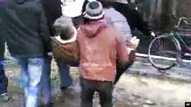 This image made from amateur video and released December 27, 2011, purports to show men carrying an injured man in Homs, Syria, December 26, 2011.