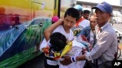 Demonstran anti-pemerintah Thailand membawa demonstran yang terluka dari bis ke ambulance pasca serangan kelompok bersenjata di Bangkok (1/4).