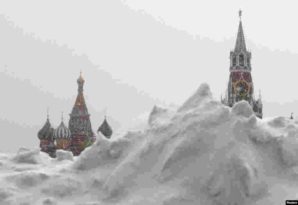 A pile of snow is seen in Red Square during a snowfall in central Moscow. St. Basil's Cathedral (L) and the Spasskaya Tower of the Kremlin are seen in the background.