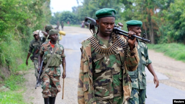 Congolese M23 rebels carry their weapons as they patrol near Rushuru, in Democratic Republic of Congo, Aug. 3, 2013.
