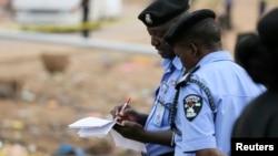 Policemen take down evidence at the scene of a car bomb attack in Nyanya, Abuja, May 2, 2014.