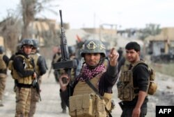 FILE - Members of Iraq's elite counter-terrorism service secure the central Ramadi's Hoz neighborhood after Islamic State jihadists abandon their last stronghold in the Anbar province capital, Dec. 27, 2015.