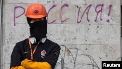 یک تظاهرکننده طرفدار روسیه در بیرون ساختمان دولتی در شرق اوکراین کشیک می دهد - دونستک، ۱۹ آوریل