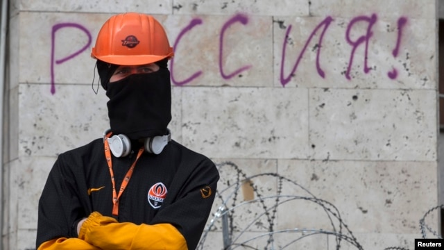 A masked pro-Russia protester stands guard at a barricade outside a regional government building in Donetsk, eastern Ukraine on April 19, 2014.