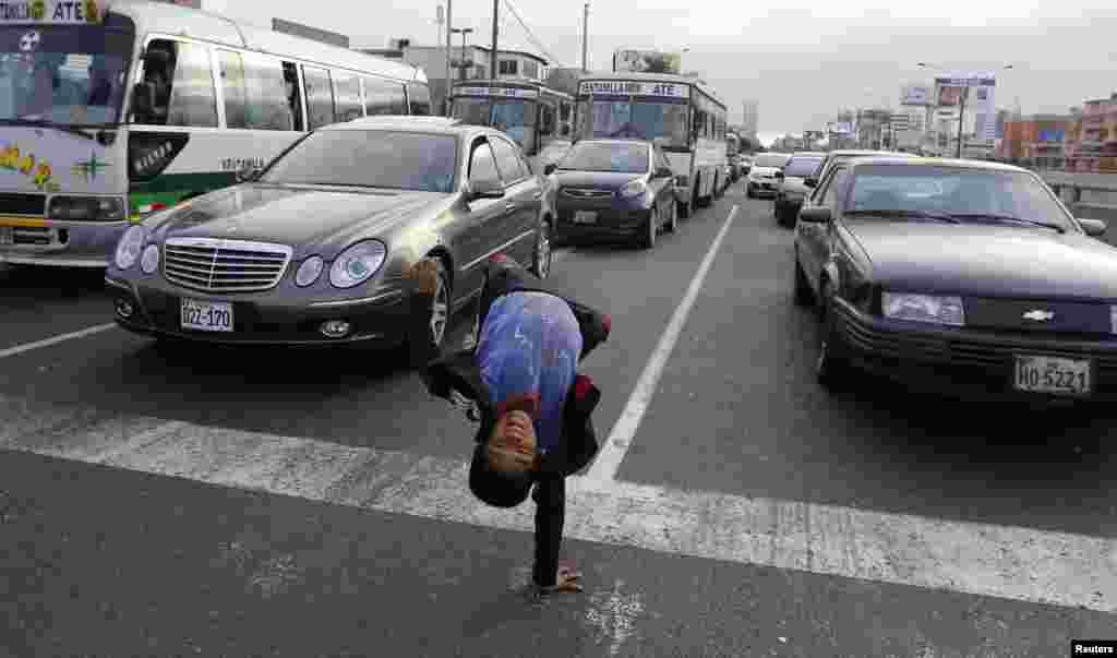 Renzo, 11, somersaults at a traffic junction in the San Borja district in Lima, Peru, Aug. 18, 2014.