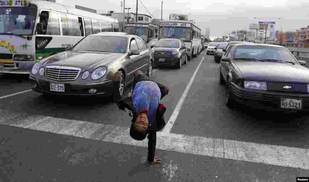 Renzo, 11 anos, faz um salto mortal em pleno trânsito em San Borja, um distrito em Lima, Peru.