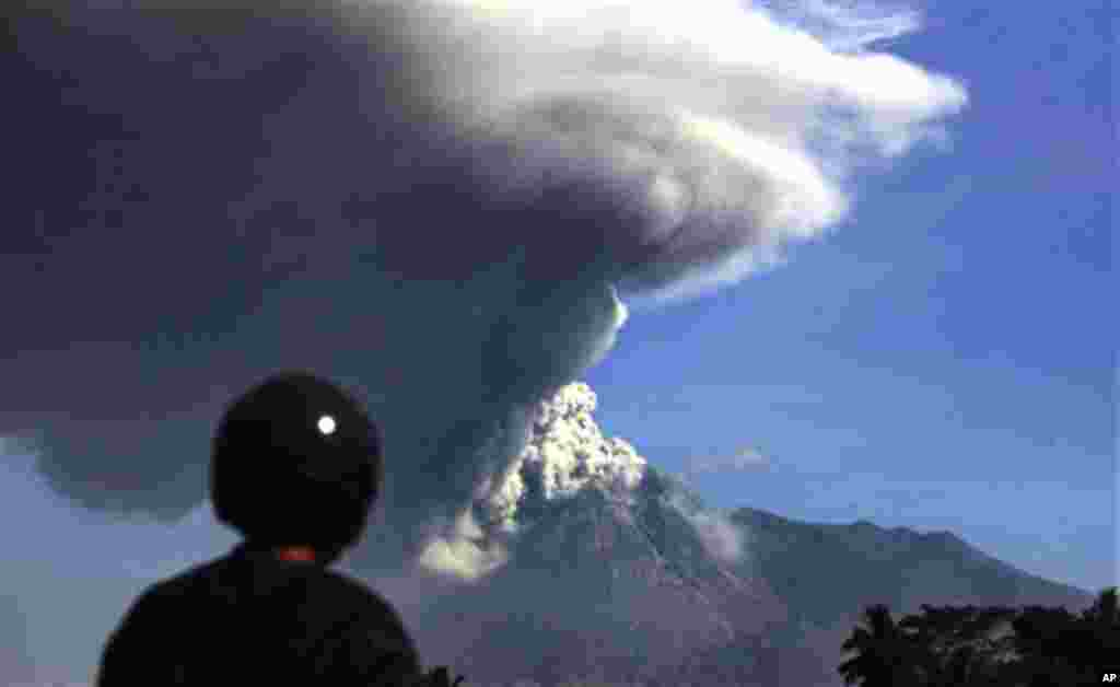 A man watches Mount Merapi spews volcanic material as seen from Argomulyo, Indonesia, Friday, Nov. 12, 2010.(AP Photo/Achmad Ibrahim)