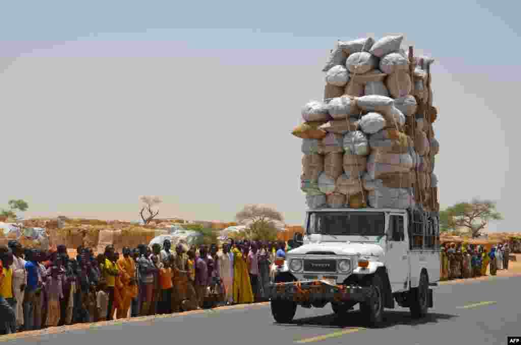 Carro sobrecarregado passa pelo campo de refugiados de Assaga na fronteira entre o Níger e a Nigéria.