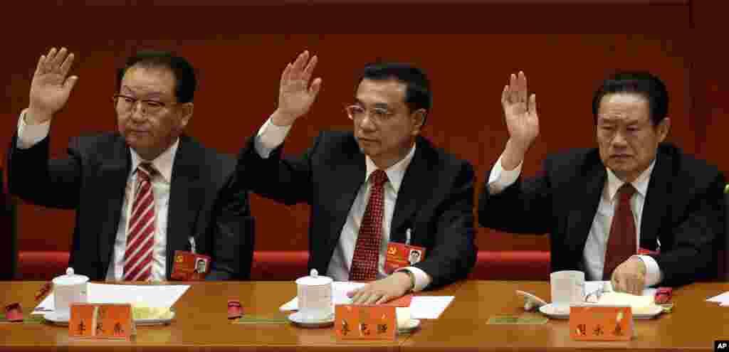Chinese Vice Premier Li Keqiang, center, Propaganda chief Li Changchun, left, and head of Political and Legislative Affairs Committee Zhou Yongkang raise their hands during the 18th Communist Party Congress, Beijing, November 14, 2012.