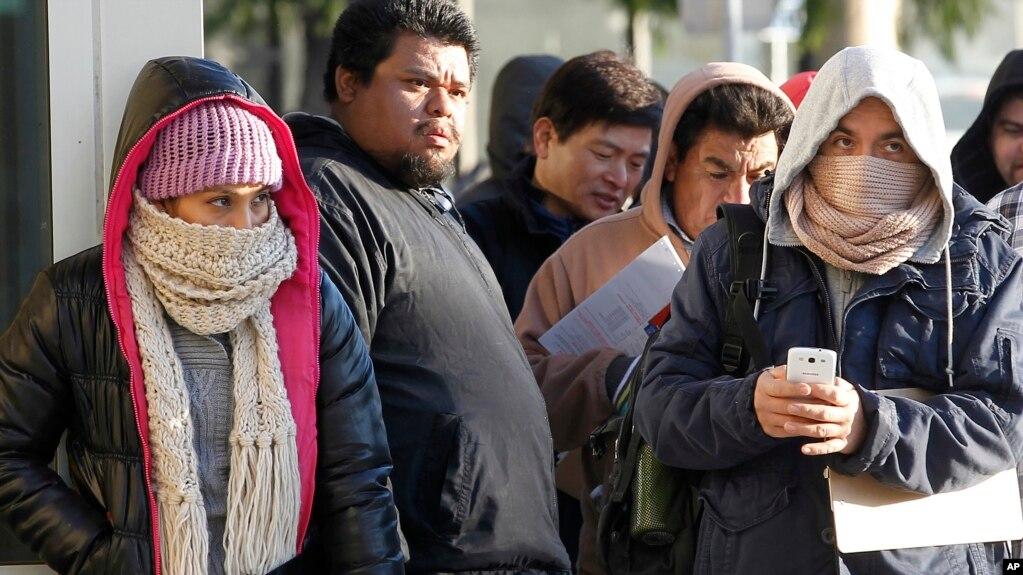 Tư liệu - Người nhập cư chống chọi thời tiết lạnh đứng xếp hàng bên ngoài văn phòng Sở quản lý Xe Cơ giới California để đăng ký bằng lái xe ở Stanton, California, ngày 2 tháng 1, 2015.