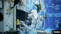 FILE - Astronauts practice on a Hubble model underwater at the Neutral Buoyancy Lab in Houston under the watchful eyes of NASA engineers and safety divers. China aims to build a deep-sea lab that provides long-time living and working space for scientists.