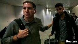 19일 미국 기자 글렌 그린월드(왼쪽)가 그의 동성 연인 데이빗 미란다와 함께 리오데 자네이로 국제공항을 빠져나오고 있다.