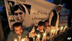 巴基斯坦人10月15日在白沙瓦一面印有优素福扎伊肖像的旗帜前点燃蜡烛