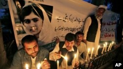 Pakistanis light candles in front of a banner showing a picture of 14-year-olschoolgirl Malala Yousufzai in Peshawar, Pakistan, Oct. 15, 2012.