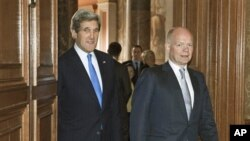 Menlu AS John Kerry (kiri) didampingi Menlu Inggris William Haquw (kanan) setibanya di kantor Kemenlu Inggris, London (10/4).