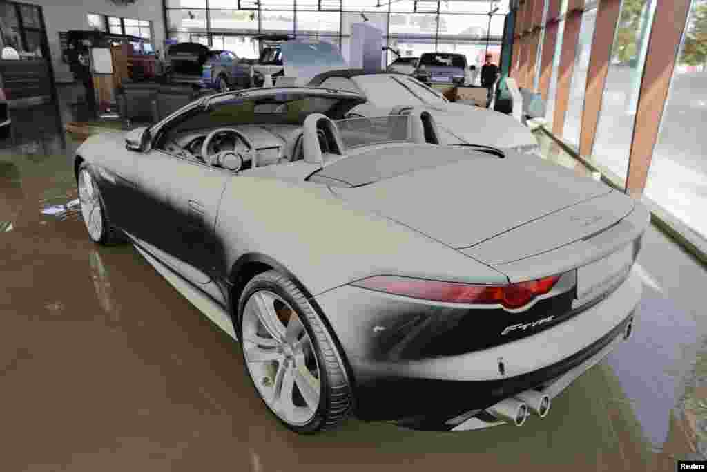 A new Jaguar convertible stands in a showroom covered with a thin film of mud after the floods of the nearby Danube river subsided in Fischerdorf, Germany, June 9, 2013.