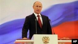 Vladimir Putin meletakkan tangannya di atas konstitusi Rusia saat dilantik kembali sebagai Presiden Rusia untuk masa jabatan yang ketiga di Moskow (7/5).
