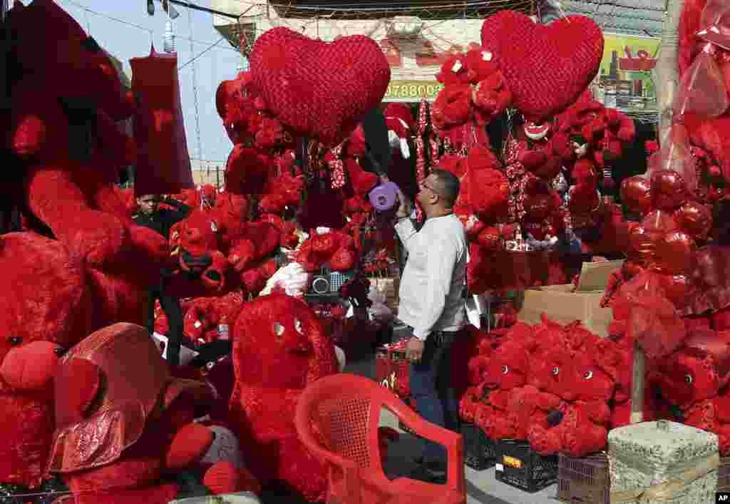 Một chủ cửa hàng làm sạch hàng hóa trước Ngày Valentine trong khu vực Karrada của Baghdad, Iraq.