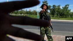 Cảnh sát Trung Quốc cấm chụp hình tại một chốt kiểm soát trên đường đến thị trấn Lukqun của người Hồi giáo Uighur trong tỉnh Tân Cương.
