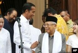 Petahana Presiden Joko Widodo (tengah kiri) bercanda dengan cawapres Ma'ruf Amin (tengah kanan) dalam konferensi pers setelah pertemuan dengan partai koalisi di Jakarta, 18 April 2019.
