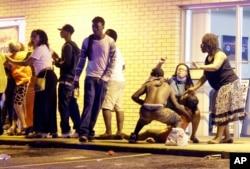 Warga membantu seorang perempuan yang histeris setelah sebuah tembakan terdengar dekat sebuah demonstrasi di Ferguson, Missouri, MInggu (9/8).