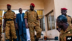 Burkina Faso Lt. Col. Issac Yacouba Zida, center, leaves a government building after meeting with political leaders in Ouagadougou, Burkina Faso, Nov. 4, 2014.