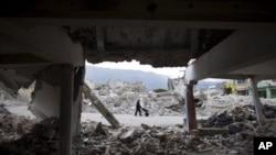 A man pushes a wheelbarrow past earthquake damaged buildings in downtown Port-au-Prince.