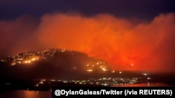 Asap membubung dari api kebakaran hutan tampak di Highway 3 dekat Kota Osoyoos, British Columbia, 20 Juli 2021. (Foto: Twitter @DylanGaleas via Reuters)