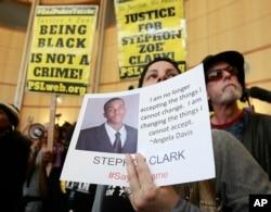 지난 18일 캘리포니아주에서 흑인 청년 스테폰 클라크가 아이폰을 총으로 오인한 현지 경찰의 총에 맞아 사망하는 사건이 발생한 가운데, 22일 새크라멘토에서 열린 항의시위에 참여한 여성이 스테폰 클라크의 사진을 들고 있다.