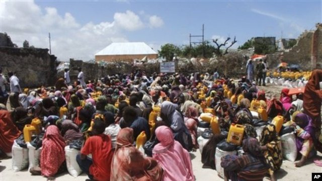 Somalis from southern Somalia receive food distributed by the Muslim Aid Organization in Mogadishu, Somalia, Thursday, Aug. 4, 2011.