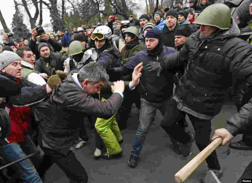 Anti-government protesters attack a deputy of the Party of Regions Vitaly Grushevsky (2nd L, front) outside the Ukrainian Parliament building in Kyiv.