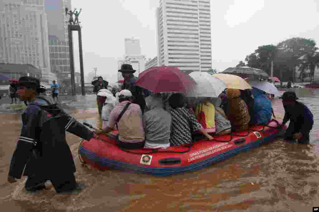 Firefighters help people on a rubber boat in a flooded street, Jakarta, Indonesia, January 17, 2013.